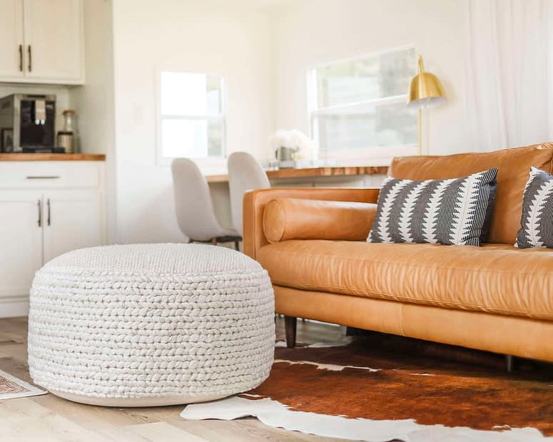 Large pouf for living room in front of a leather sofa