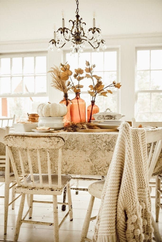 Thanksgiving table centerpieces with neutral linens and amber bottles filled with dried stems