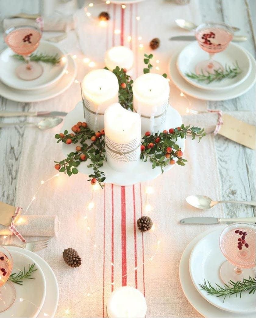 Christmas centerpiece using a red striped runner and a cakestand with candles on top