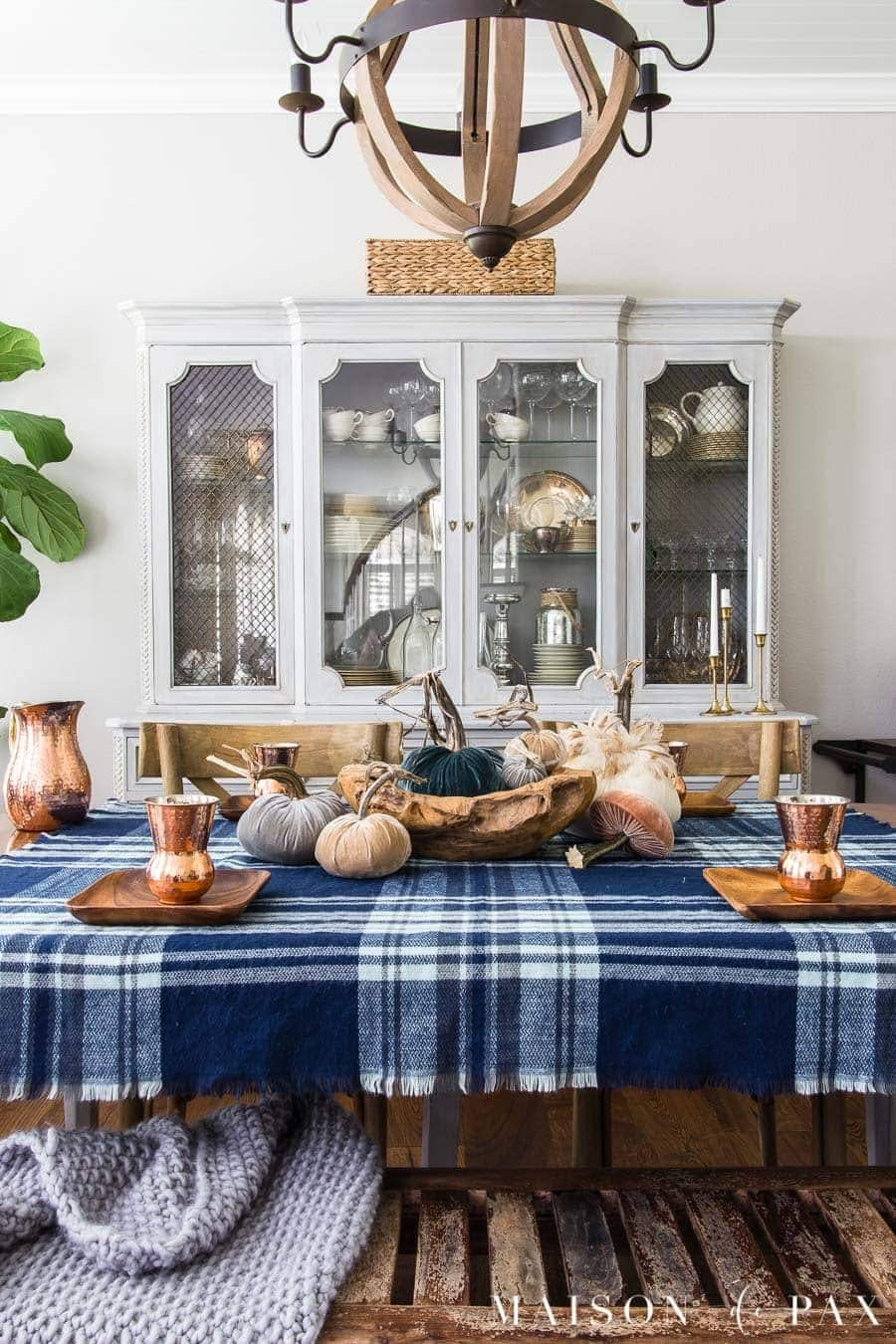Thanksgiving table centerpieces with blue plaid tablecloth, acaia bread bowl and mini pumpkins