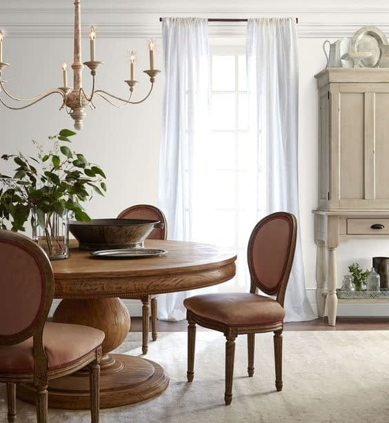 a dining room with white painted walls and wood table and chairs