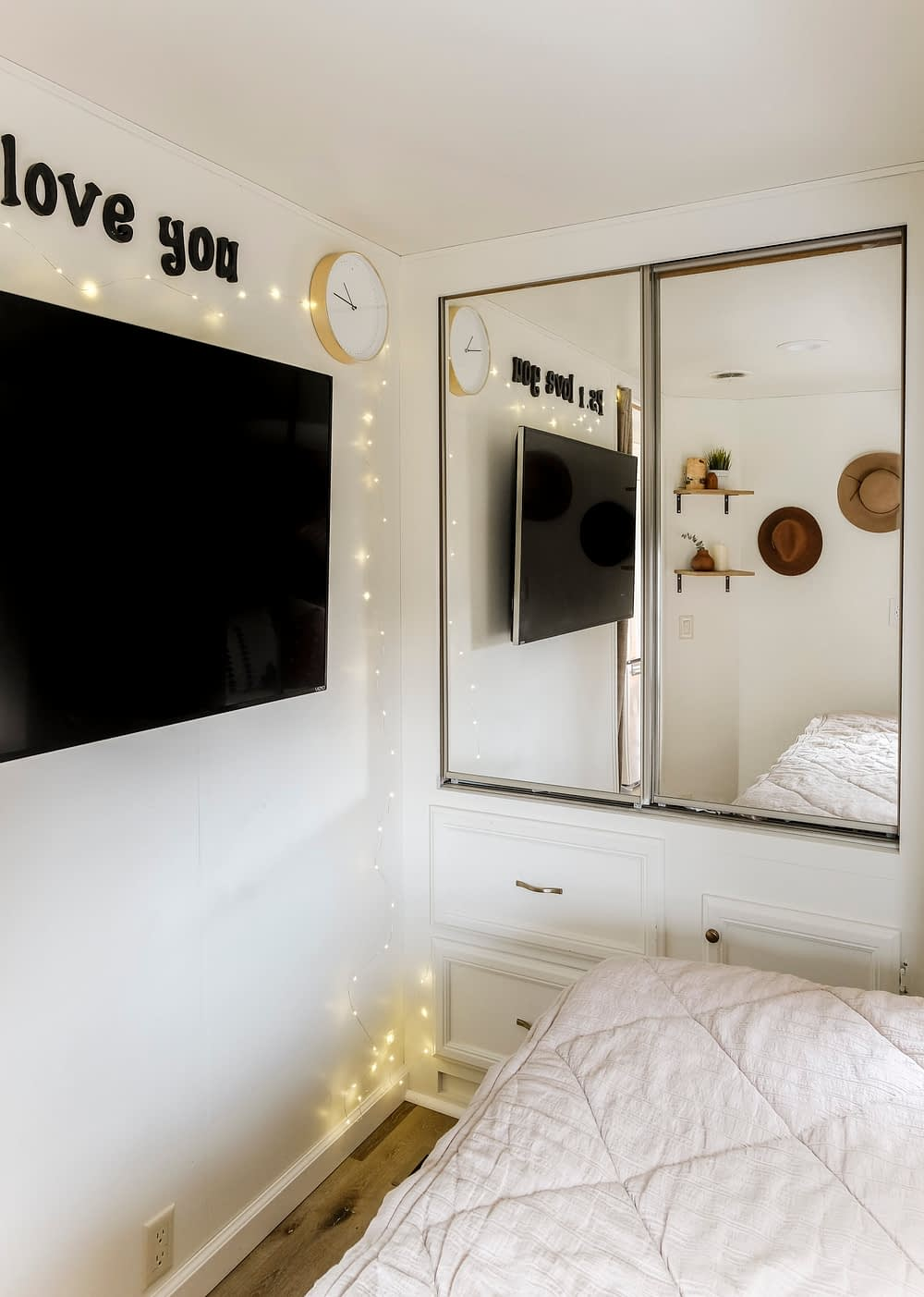 RV bedroom with wall mounted TV and mirrored door closets