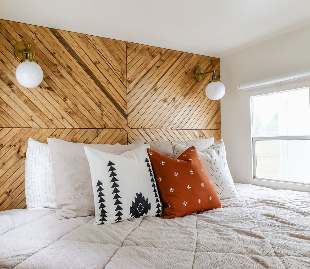 RV bedding and throw pillows in front of a wood accent wall
