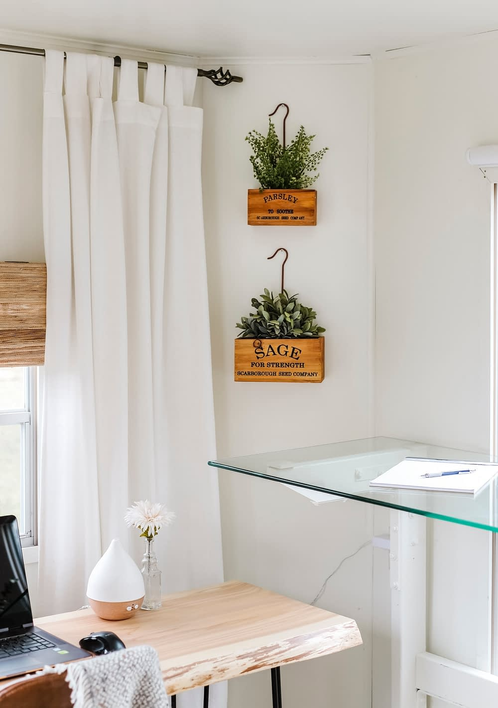 Wood herb planter boxes hung on the wall above home office desktop