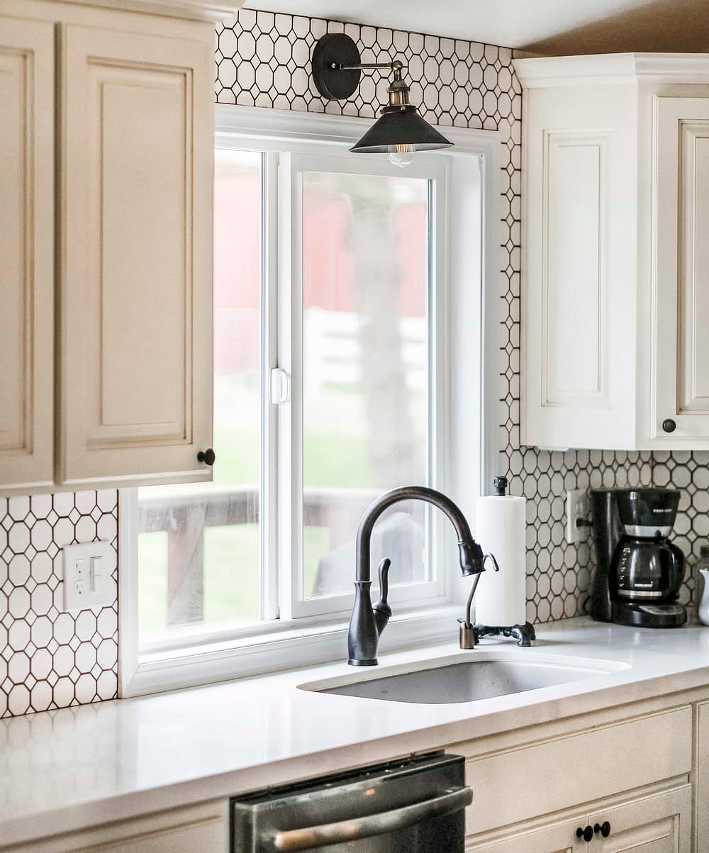 White kitchen with an industrial wall sconce above farmhouse sink