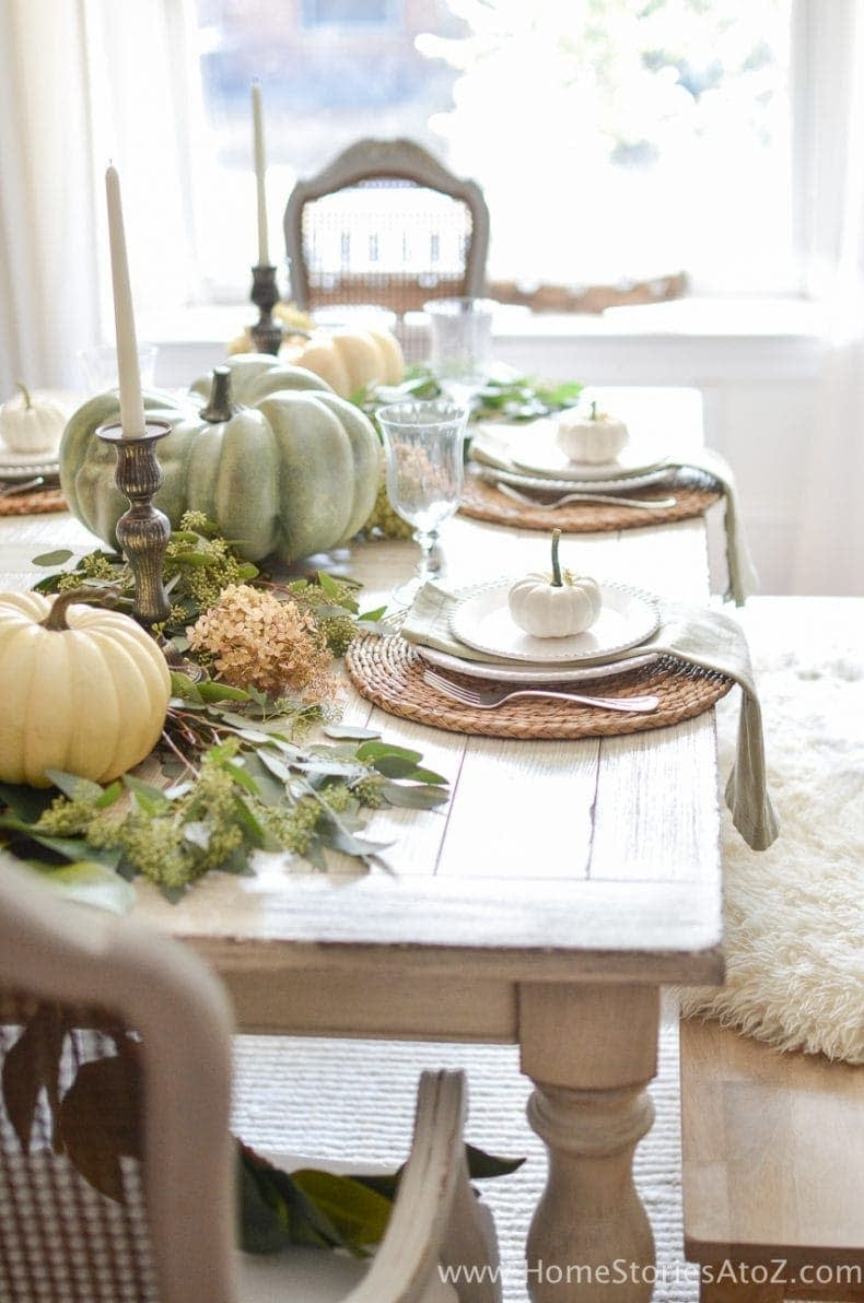 Thanksgiving table centerpieces with large gourds and round chargers